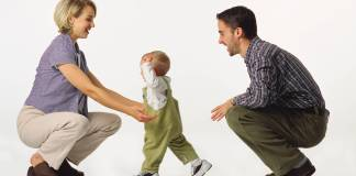Bambino compie i suoi primi passi tra il papà e la mamma