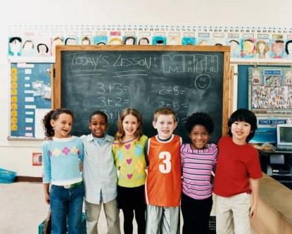 Bambini delle elementari in fila davanti alla lavagna