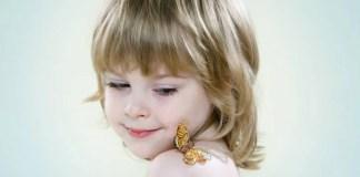 bambina con una farfalla posata sulla spalla