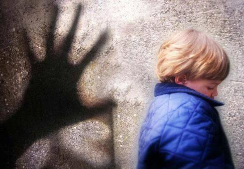 Bambino spaventato dalla presenza dell'ombra della mano di un uomo