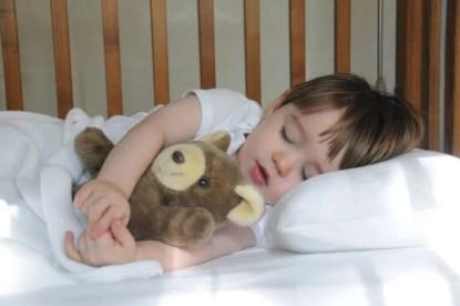 Bambino che dorme con orsacchiotto