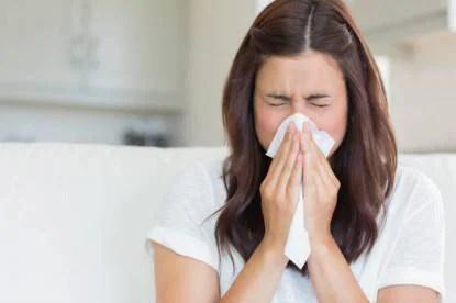 Donna con il raffreddore si soffia il naso (influenza)