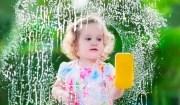 Little girl washing a window