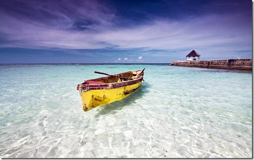 Fishing canoe docked at a beach in clear shallow water, north coast Jamaica