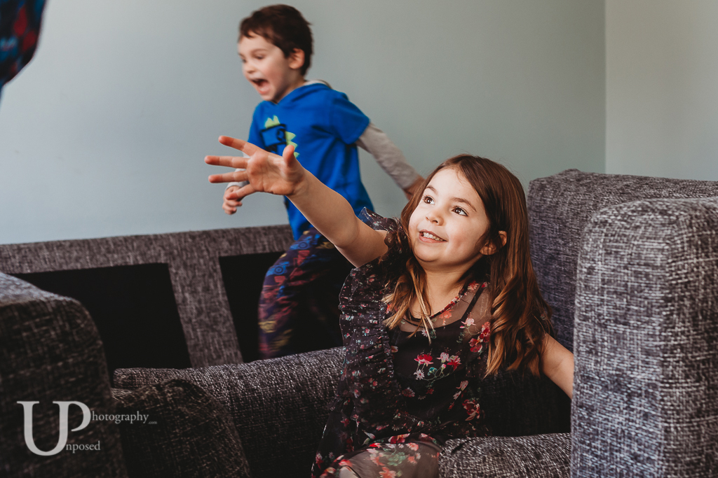 A young girl reaching out for her parent with a young boy running over furniture in the background.