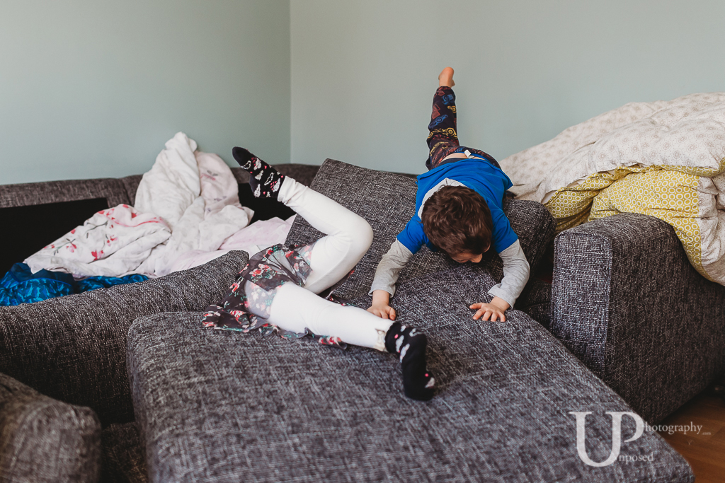 Young boy and girl jumping over a soft cushions after making a den indoors.