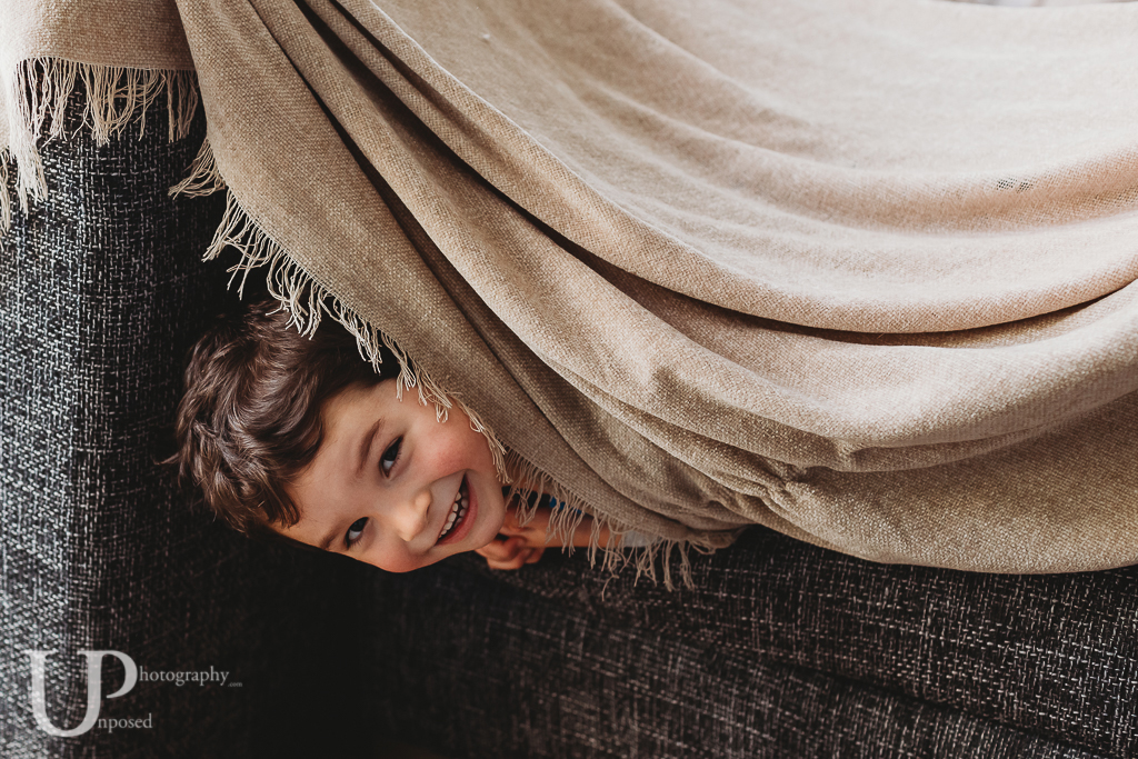 Young boy looking out from under a blanket on a den built inside.