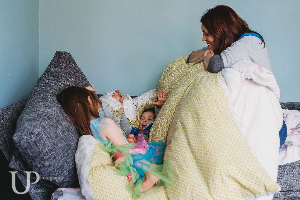 A young boy engulfed by a duvet with a mother and young girl beside him.
