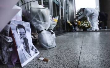 डॉ. ली वेनलिआंग के फोटो के सामने फूलों के साथ शोक संवेदना व्यक्त करते लोग।