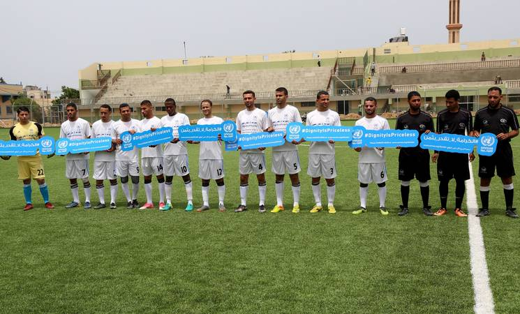 """Under the slogan """"Dignity is Priceless"""", the UNRWA Gaza Field Office organized a friendly football match between UNRWA local staff and Palestine refugee youth on 4 May at Al Durrah Stadium in Deir Al Balah, central Gaza. © 2018 UNRWA Photo by Khalil Adwan."""
