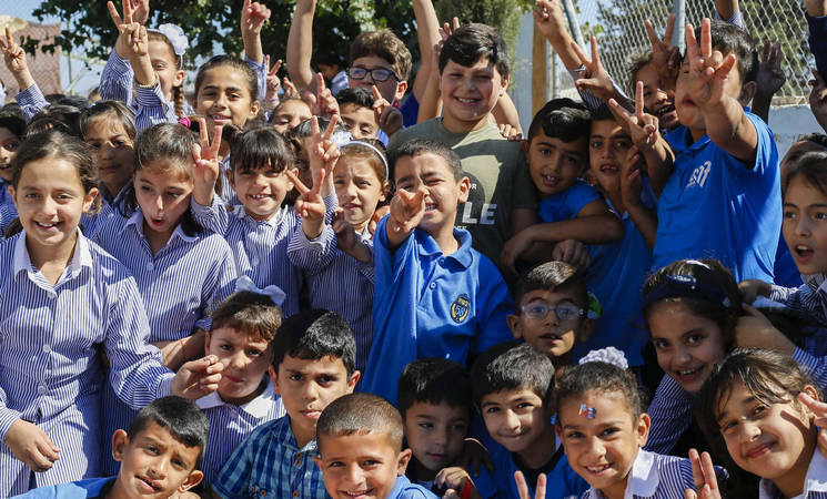 Girls and boys attending UNRWA schools in the Jalazone Palestine refugee camp in the West Bank wave during a break in their lessons. © 2018 UNRWA Photo by Marwan Baghdadi.