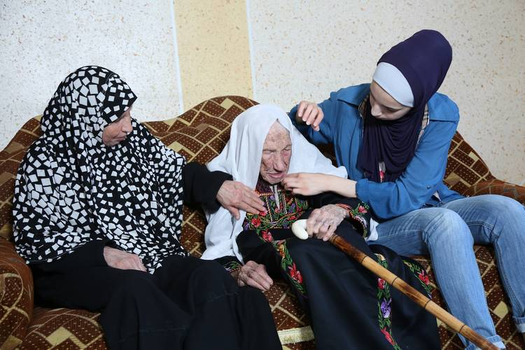 65-year-old Zainab Atallah, Hakma's daughter (left), 105-year-old Hakma Atallah (middle) and 19-year-old Haneen Atallah, Hakma's granddaughter (right) © 2018 UNRWA Photo by Mohammed Hinnawi.