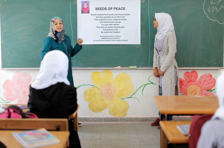 "Amani Kullab, human rights teacher and Bassma Asfour explaining to a class at Abassan Preparatory school the winning poem of the 2017 Inspiration Messages of Peace Contest, titled ""Seeds of Peace"". Photo credit: ©UNRWA Gaza 2017. Photo by Rushdi Al-Sarraj"