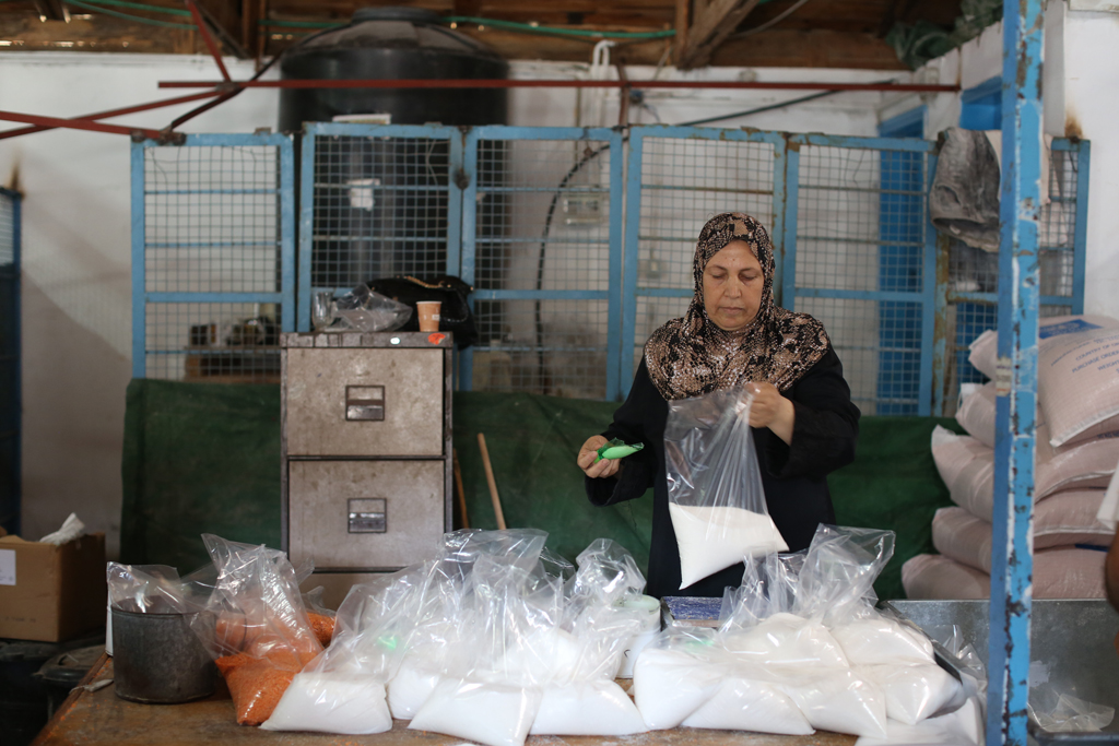 Ammna Al Najjar is packaging bags of sugar to prepare for the food distribution at Beach camp Distribution Centre in western Gaza city. © 2016 UNRWA Photo by Tamer Hamam