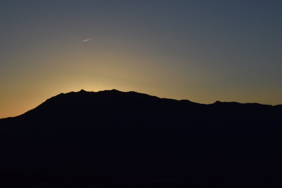Dusk, mountains silhouetted by the evening sky, and a shooting star visible overhead