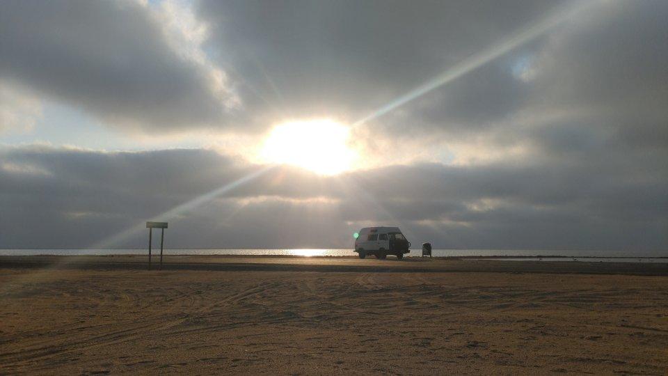 The Vanderful van at the beach, the sun low behind it