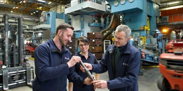 Produktion von Hirschvogel: Werkleiter und Mitarbeiter begutachten eine mehrstufig automatisch kalt umgeformete Getriebewelle. Im Hintegrund stehen mehrere Pressenaggregate.