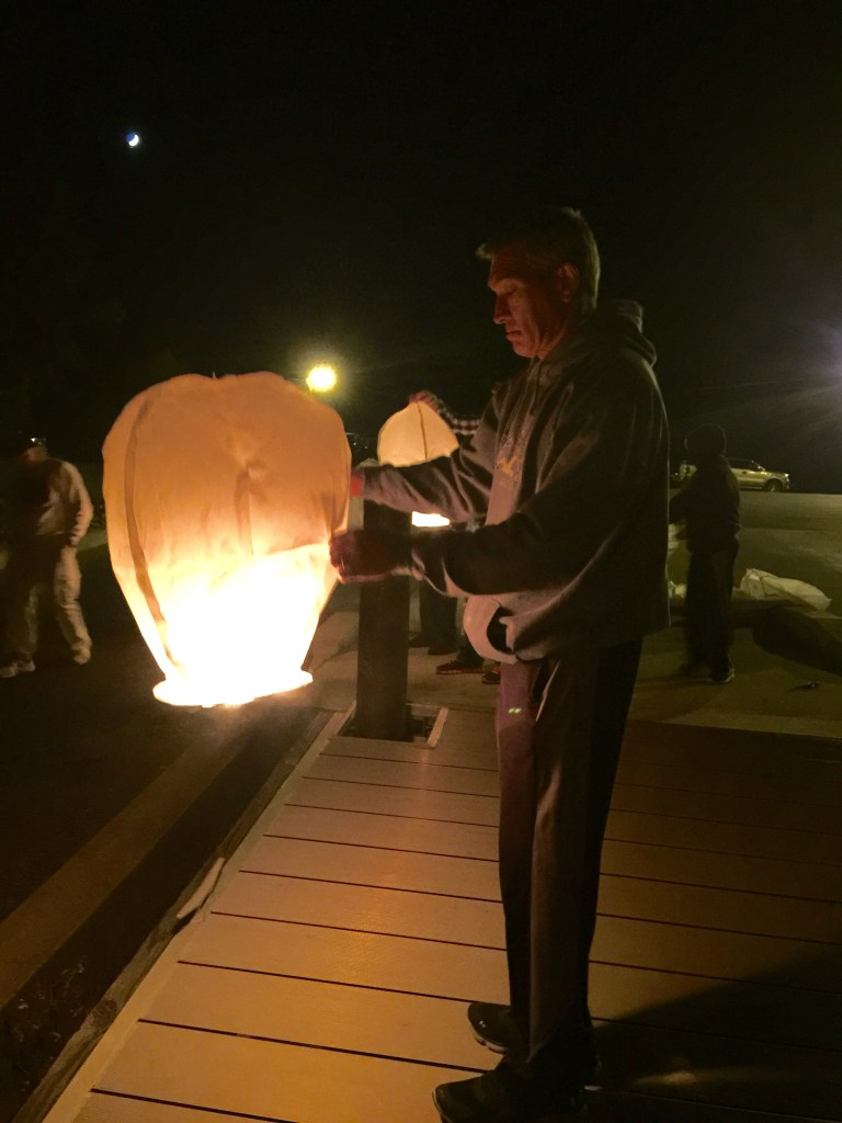 A father lights a lantern in memory of his son