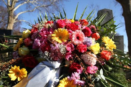 Kranz mit Nelken Rosen und Gerbera am Grab mit blauem Himmel