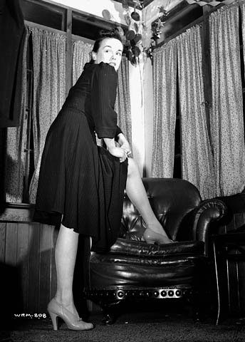 "Veronica Foster, an employee of John Inglis Co. Ltd. known as ""The Bren Gun Girl"", adjusts her stockings at the Glen Eagle Country Club. May 10, 1941. National Film Board of Canada. Photothèque / Library and Archives Canada /"