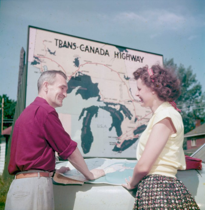 Two travellers - one man and one woman - consult a road map before the trans-Canada highway sign at the intersection of highways 15 and 17, Ottawa, Ontario