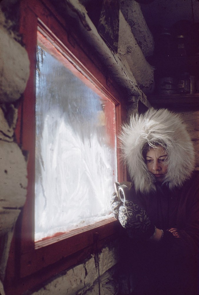 Woman (possibly Rosemary Gilliat Eaton) wearing a winter coat with a fur-trimmed hood and using photographic equipment to make images of frost on the windows. Shilly Shally Lodge, Gatineau Park