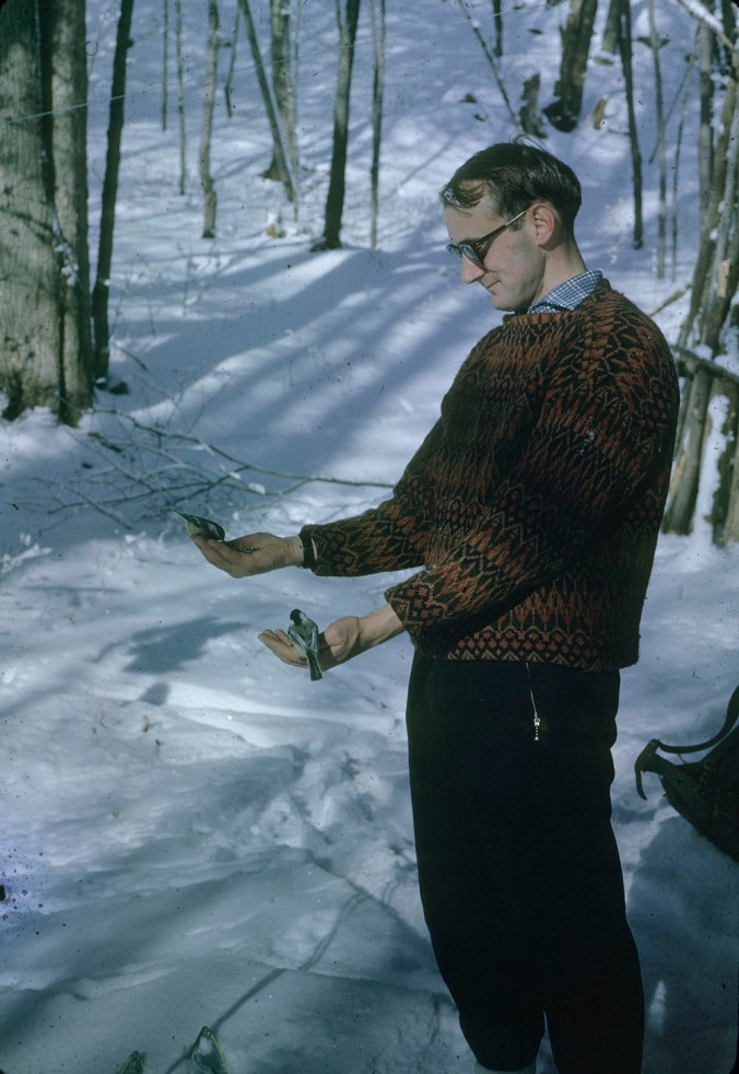 A man wearing 1960s clothing stands outside in a snow landscape. He is holding a small bird in each hand. He gazes down at them with a bemused expression.