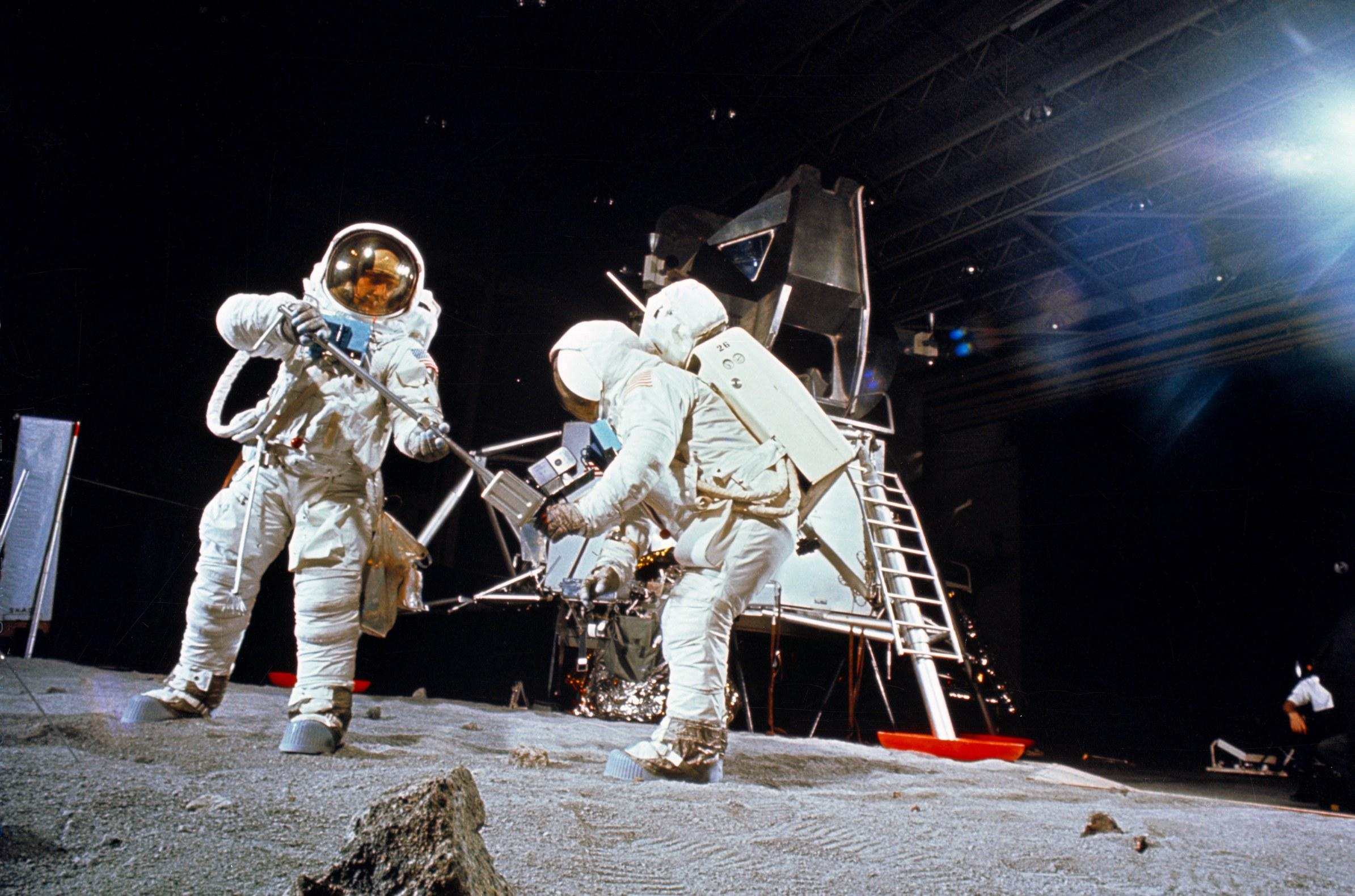 Armstrong and Aldrin practicing on fake moon dust under fake black sky