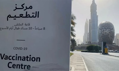 An advertisement placard informs the public of the location of a designated COVID-19 vaccination center at Dubai's financial center district, UAE