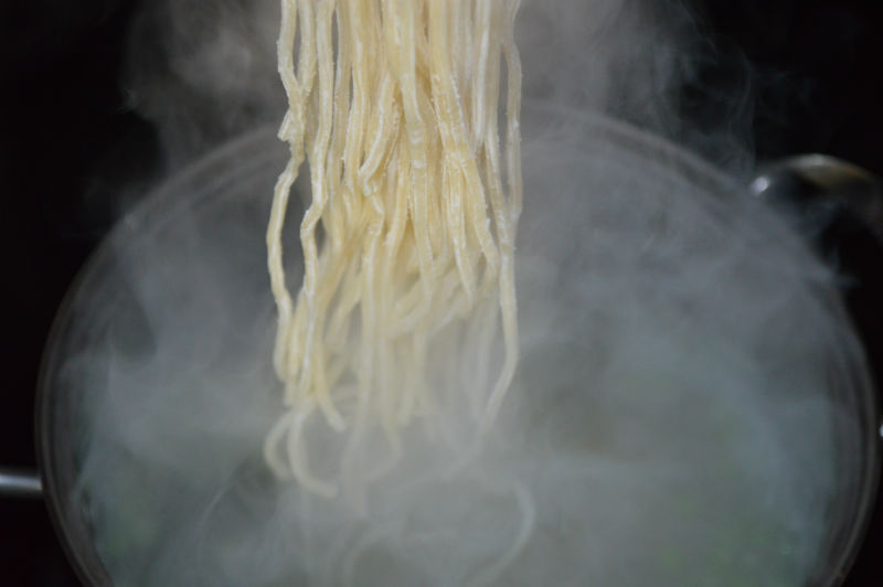 Fresh noodles cooking in boiling water