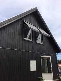 Grå fönstermarkis Java på svart hus