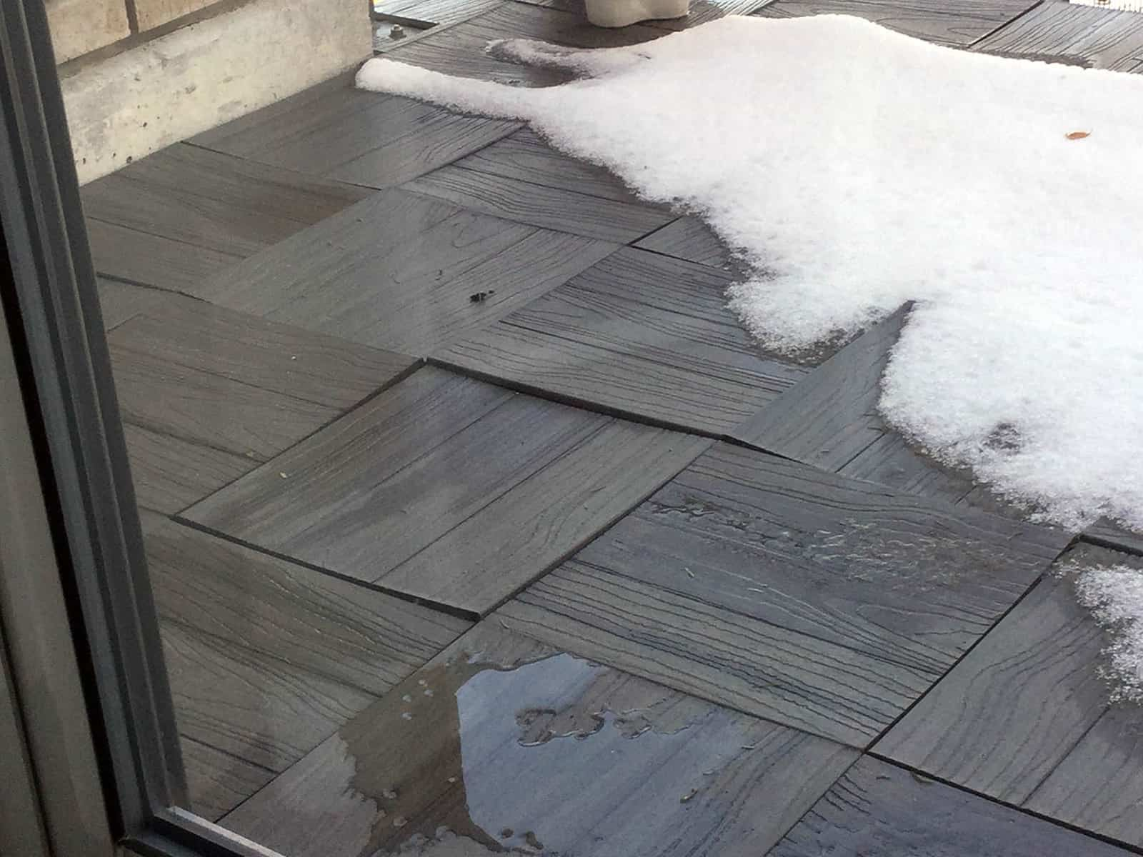 Warped Home Depot Tiles- installed only the preceding summer! Solid grey 1x1-foot WPC tiles.