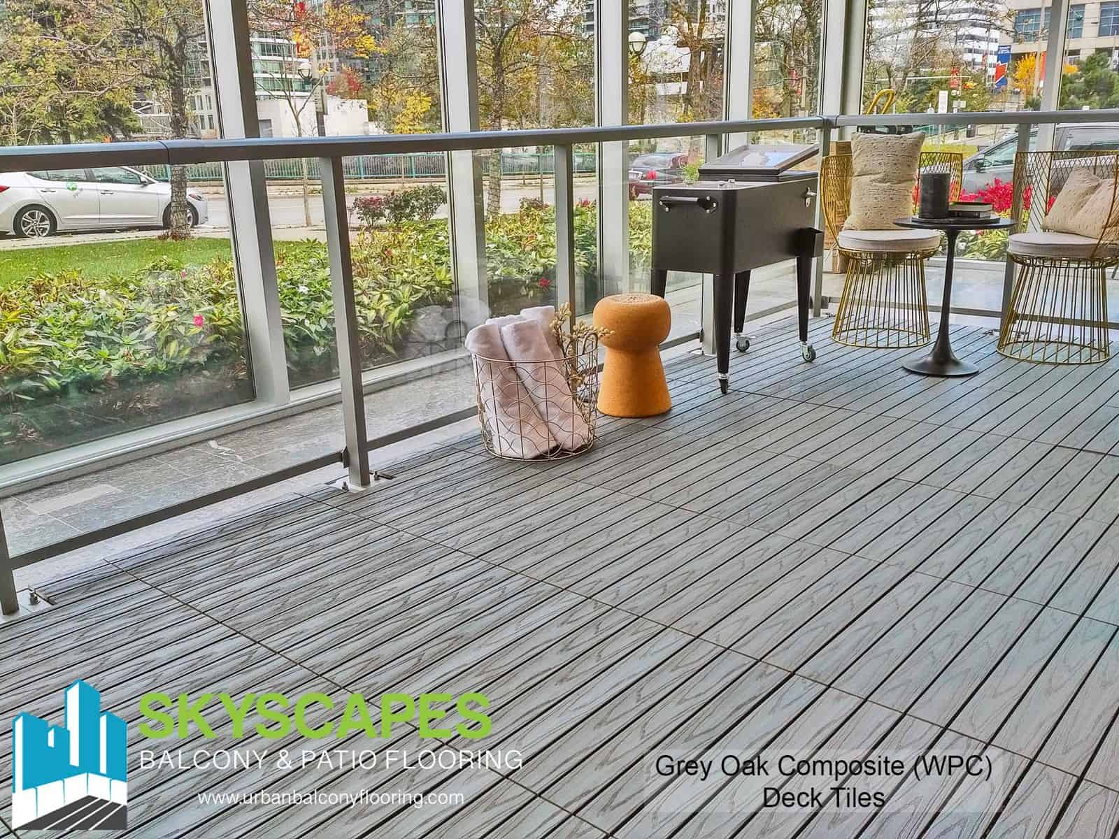 Grey oak, 4-slat, embossed WPC Tile seen on angle on indoor terrace. Each tile measures 2 by 1 feet. Skyscapes green and blue logo at bottom-left of image.