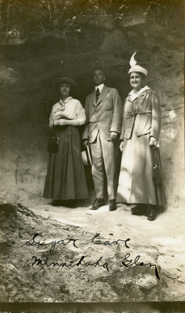 Three people from the late 19th or early 20th century, standing in a shallow cave.