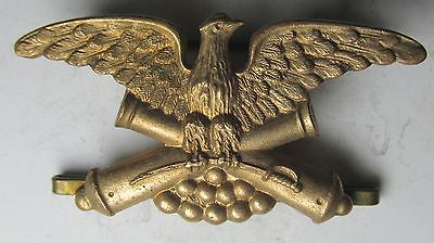 an eagle, wings spread, facing right, clutching 2 crossed cannons in its talons.