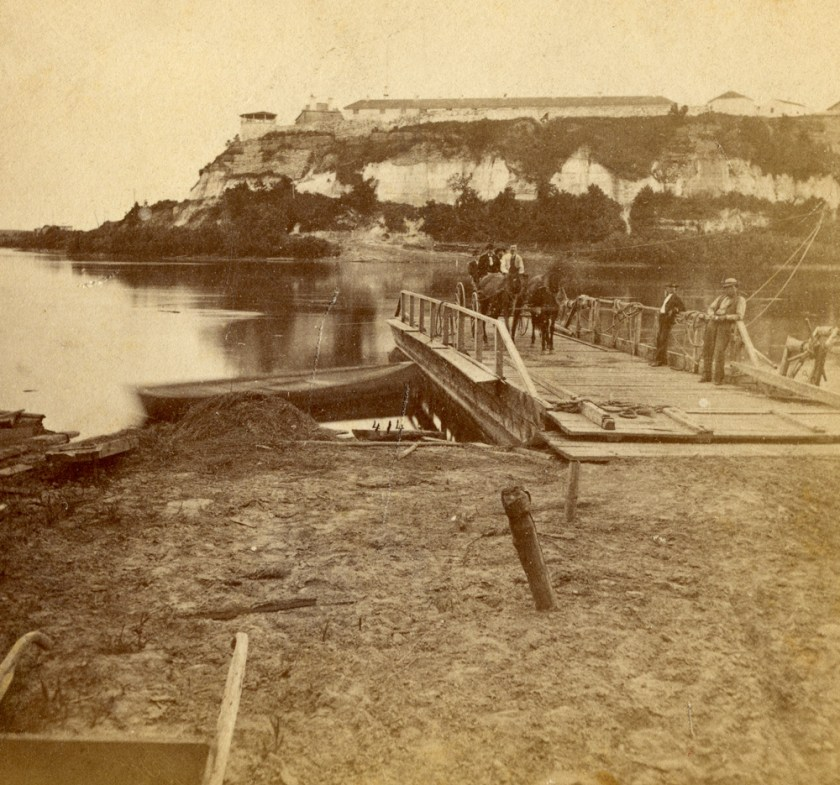 A fire of Fort Snelling in the distance with a flatbottomed ferry boat on the near shore. A wagon with a couple of people in it was on board, and a two ferrymen lounged against the ferry's railings.
