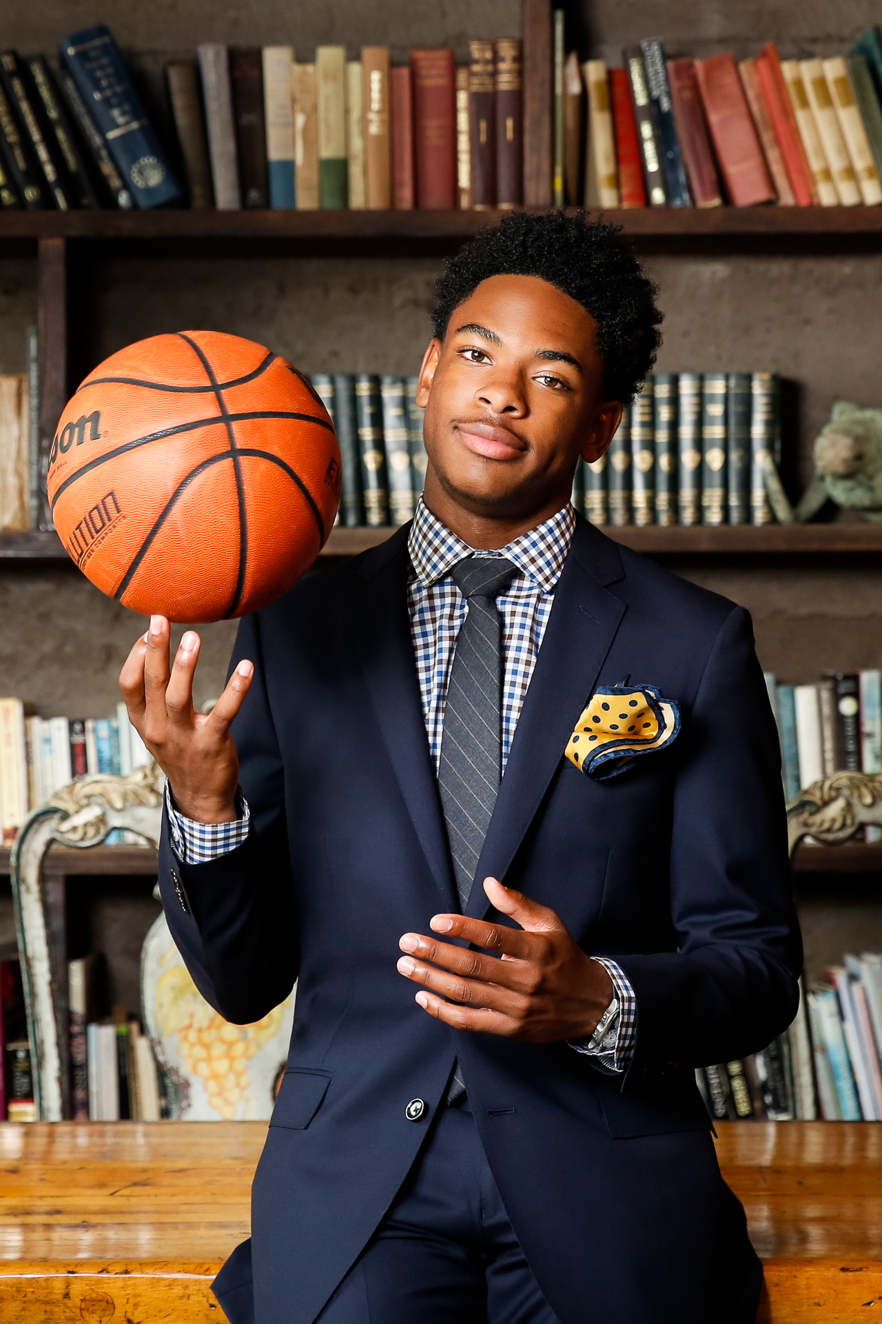 This young basketball player had all of the look and style off the court for his High School Senior portraits. His photoshoot was captured at The Goat Farm in Atlanta, GA by Starr Petronella with Urban Flair Photography. He combined his tailored suit with his love for basketball in non-traditional pictures. The African-American male is a great role model for others growing up with a similar passion.