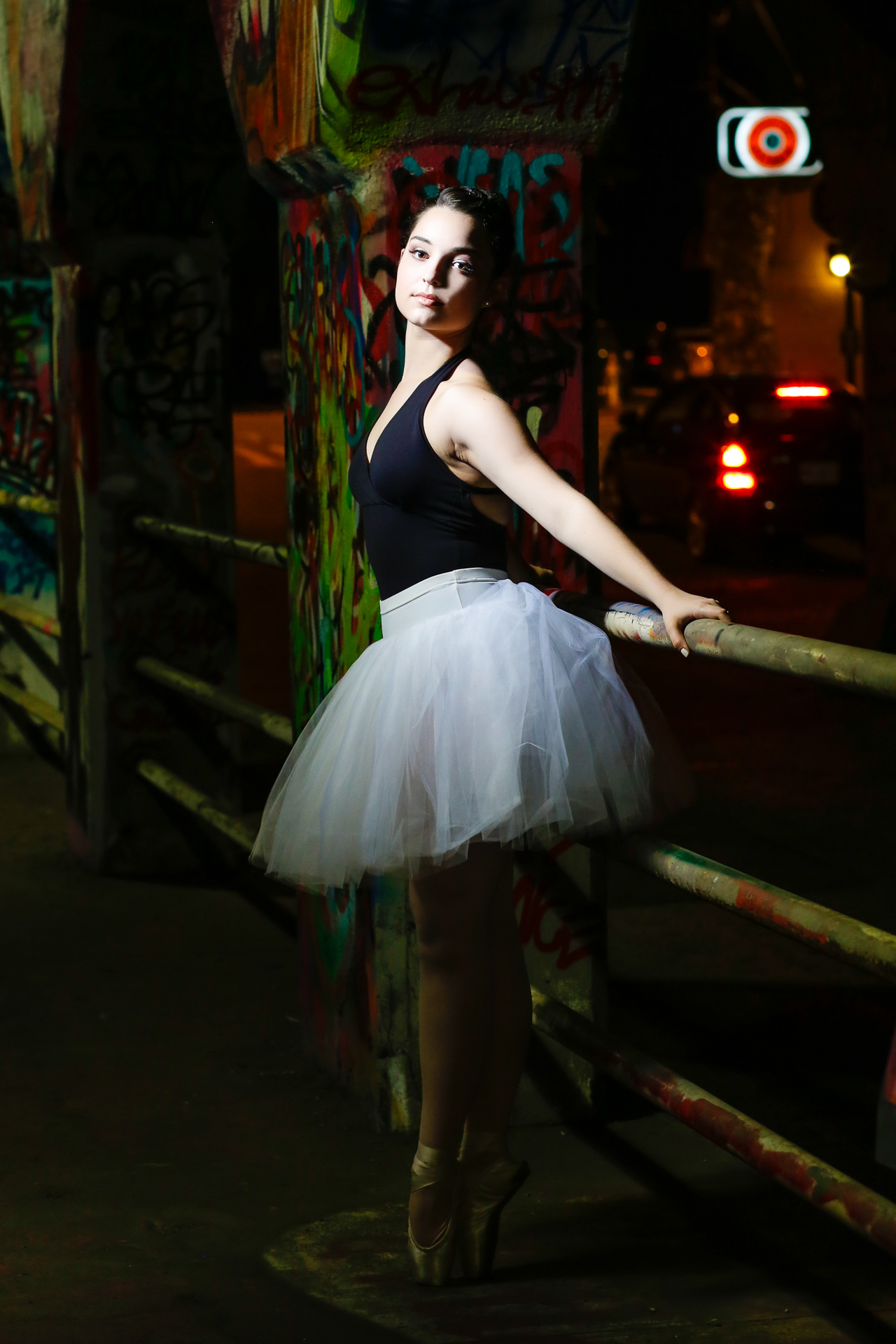 Ballerina dance pictures taken at Krog Street in Atlanta, GA. This look was inspired by Misty Copeland and her white tu-tu and black leotard. The  High School Senior session was full of dance poses and dramatic lighting. Images captures with Urban Flair Photography, Starr Petronella