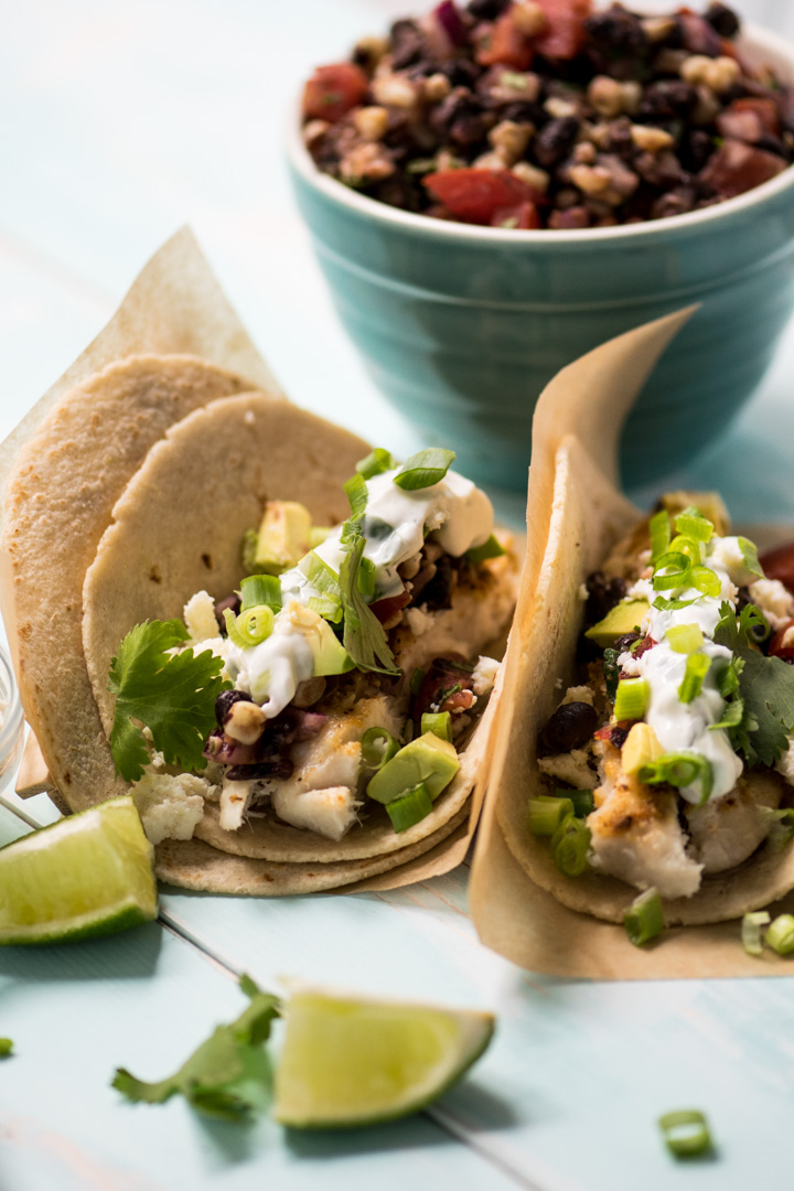 These grilled fish tacos are topped with a tangy cilantro lime sauce for a healthy weeknight meal!