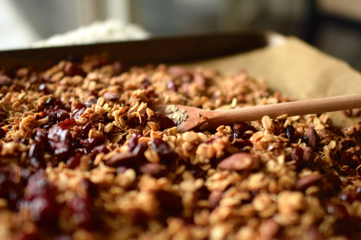 Granola with dried cranberries on a baking sheet with a wooden spoon
