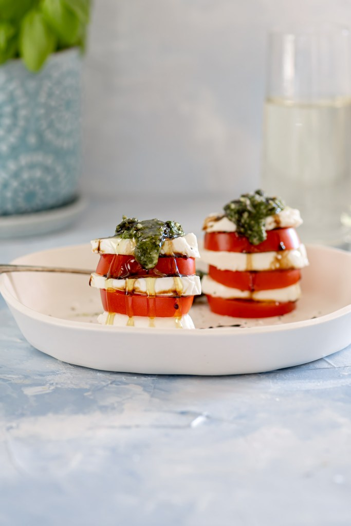 Two stacks of tomatoes and fresh mozzarella topped with pesto and balsamic glaze