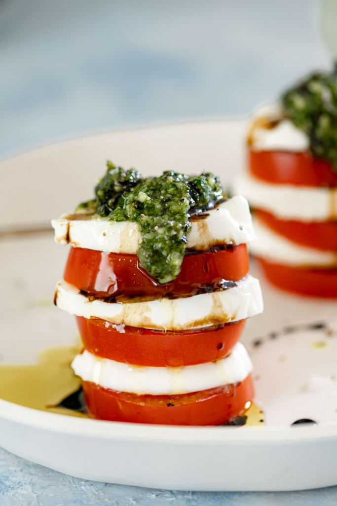 Close up of tomato, mozzarella and basil pesto stack