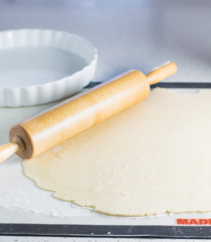 Fulled rolled quiche crust with a rolling pin at the edge