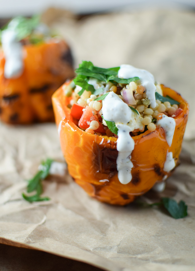 Grilled yellow bell pepper stuffed with pearl couscous, chopped veggies and drizzled with yogurt sauce