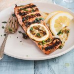 A grilled salmon filet topped with a slice of grilled lemon