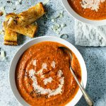 A bowl of tomato soup on a light grey background, with grilled cheese sticks on the side