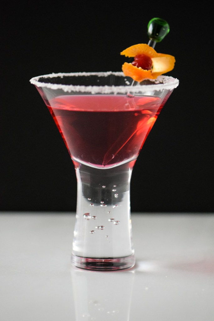 Cranberry Infused Vodka Martini in front of a black background