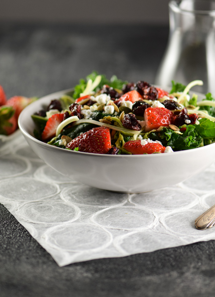 Kale salad topped with brussels sprouts, sliced strawberries, dried cranberries and goat cheese
