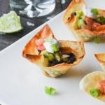 Mini wonton taco cups are filled with seasoned black bean, pico de gallo and guacamole