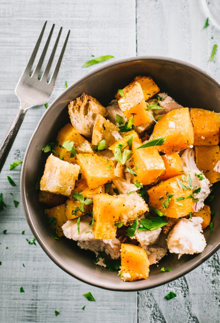 Panzanella salad of butternut squash, sourdough croutons and roasted chicken in a light grey bowl